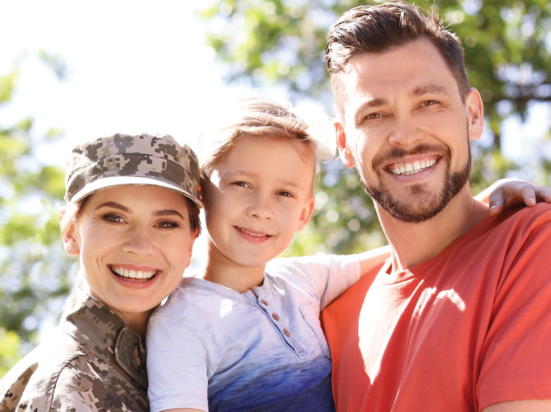 A military family smiling outside.